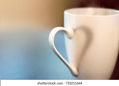 Ear mug throws a shadow in shape of heart. Idyllic moment. Cup of warm tea or coffee.