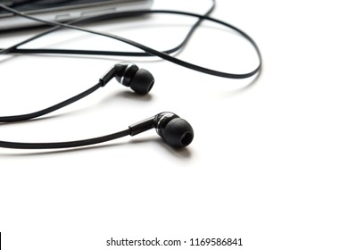 Ear plugs, headphones for listening music and sound on portable devices are connected to the smartphone on a white background.