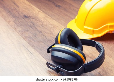 Ear protection and hard hat contruction placed on the wooden floor represents the concept of keeping the quality of hearing.