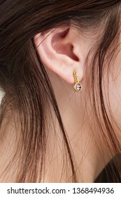Ear of Woman with gold earring chaotic hair and soft skin