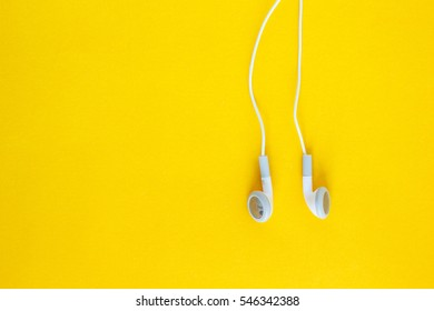 earbud or earphone on yellow background