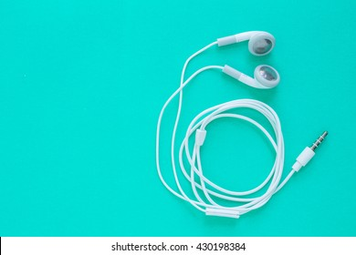 earbuds or earphones on green background