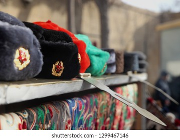 0a50a30ab1e Earflaps fur caps with red stars in a souvenir shop . Winter hats