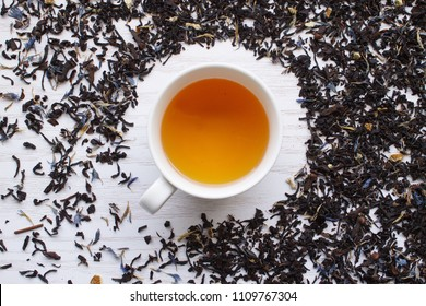 Earl Grey tea surrounded by a pile of blended loose-leaves over a white wooden surface. The tea is a  blending which has been flavoured with the addition of oil of bergamot.