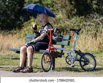EARLSWOOD, SURREY/UK - JULY 31 : Man resting on a bench holding an umbrella in Earlswood Surrey on July 31, 2020. Unidentified man
