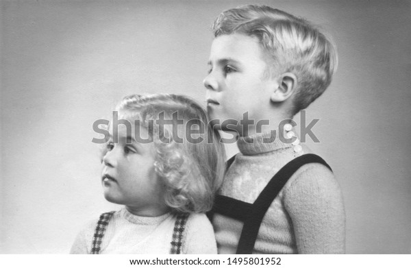 Early 1950s duo portrait of a young boy and girl with blond hair and curls looking sideways.