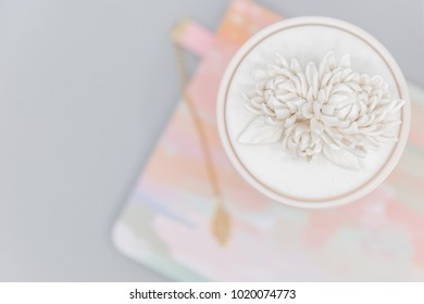 Early 2000s Anthropologie candle on an orange, pink, seafoam green, blue, and white abstract journal that has a gray background and pink / gold bookmark
