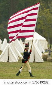 An early American flag is flown Patriot soldiers march to Surrender Field as part of the 225th Anniversary of the Victory at Yorktown, a Revolutionary reenactment Virginia, Revolutionary War.