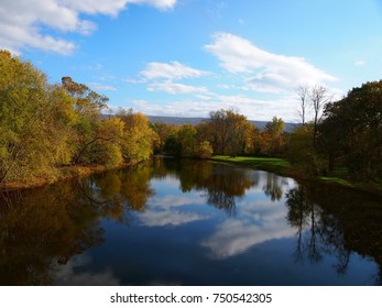 An early autumn landscape and beautiful blue sky with clouds are reflected vibrantly in a river.