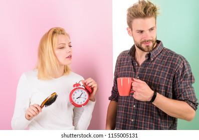 Too early awakening. Couple oversleep awakening hold alarm clock. Couple sleep not enough time. Family drink morning coffee drowsy faces. Hate morning awakening. Harmful habit to oversleep.