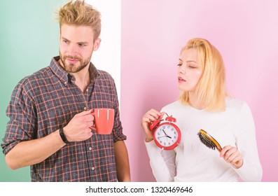 Too early awakening. Couple oversleep awakening hold alarm clock. Couple sleep not enough time. Family drink morning coffee drowsy faces. Hate morning awakening. Harmful habit to oversleep.