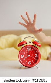 Early awakening on the alarm clock. The hand reaches for the alarm clock