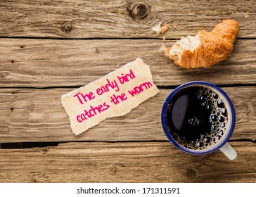 The early bird catches the worm, an inspirational saying hand written on a small torn piece of paper alongside an early breakfast of frothy espresso coffee and a half devoured fresh golden croissant