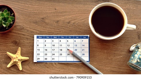 early booking dreams: a cup of coffee, calendar sheet, pencil, dried starfish, succulent plant in a pot with the ground, a souvenir from the seaside resort of the bottle with blue sand and seashells
