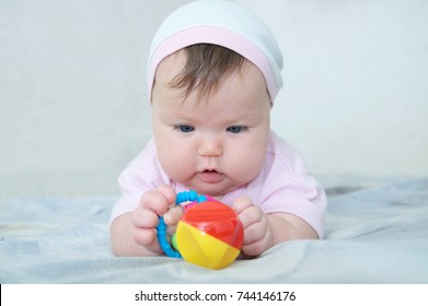 Early brain development. concentrated little baby girl  playing with rattle lying on bed