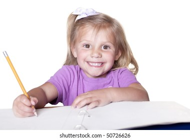Early childhood education. Cute smiling little girl learning to write.