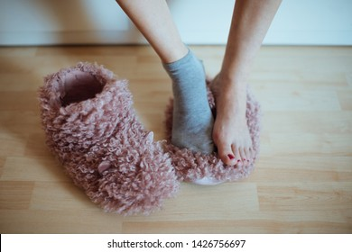 Early cold morning wake up! Woman's feet  standing on one (of two) home plush slippers - woman wearing only one sock