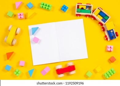 Early education background. Wooden train, car, colorful bricks and blocks with open blank notebook on yellow background
