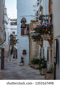 Early evening street view of Medieval city of Locorotondo, Italy with a suspended Witch Doll during the days of Lent. Locorotondo, Puglia, Italy, March 15th 2019