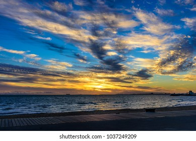 An early evening view of St Kilda beach against a dramatic blue and yellow sunset in Melbourne, Victoria, Australia
