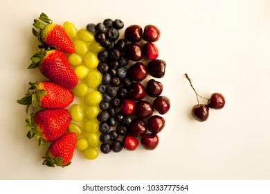 Early fruits on white work surface: strawberries, grapes, blue berries, and cherries