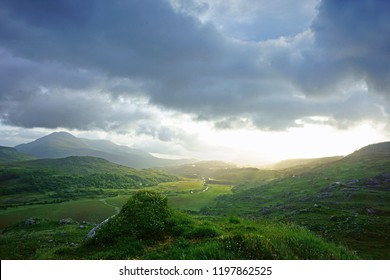 Early light and the beautiful landscape of Moll's Gap in The Ring of Kerry, Ireland, showing an early morning misty sunrise and how the clouds and shadows roll over the mountains.