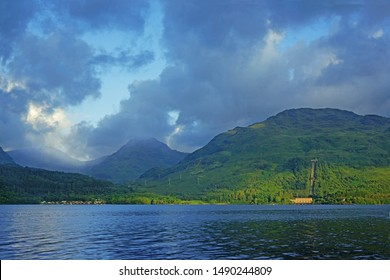 Early light and low misty clouds clip the summit of Ben Vane and Ben Narnain, viewed across Loch Lomond from Inversnaid, Stirlingshire, Scotland.