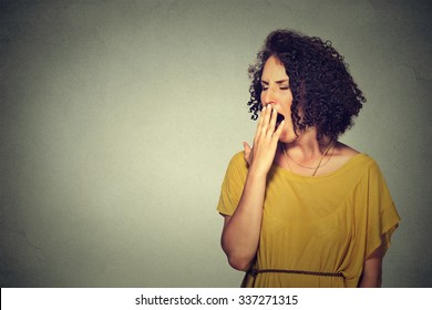 It is too early for meeting. Closeup portrait sleepy young woman with wide open mouth yawning eyes closed looking bored isolated grey wall background. Face expression emotion body language