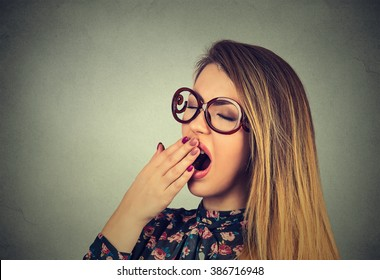 It is too early for meeting. Closeup portrait sleepy young woman with wide open mouth yawning eyes closed looking bored isolated on gray wall background. Face expression emotion body language