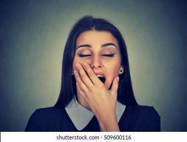 It is too early for meeting. Sleepy young woman with wide open mouth yawning eyes closed looking bored isolated on gray background. Face expression emotion body language