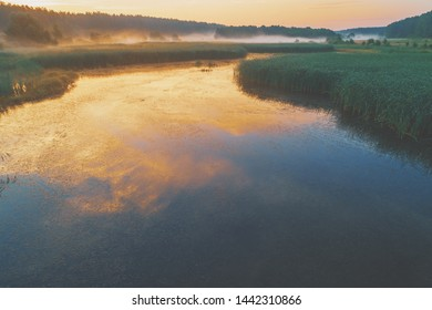 Early misty morning, sunrise over lake. Rural landscape in summer. Aerial view