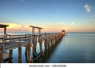 Early moonset and sunrise over the Naples Pier on the Gulf Coast of Naples, Florida in summer.