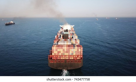 Early morning aerial view of Mega large ULCV container ship sails on open water fully loaded with containers and cargo - 366m long 145K ton