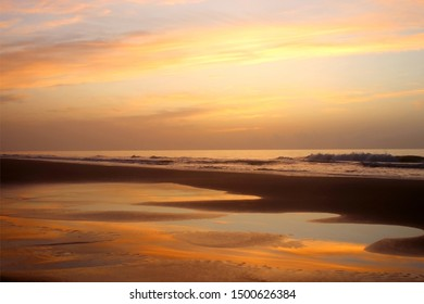 Early morning at the Atlantic beach.Marine background with beautiful colorful sky reflects in a shallow water during low tide before sunrise. Scenic seascape at the Pawleys Island, South Carolina,USA.