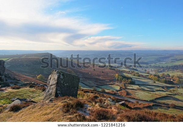 The early morning autumnal sun brightens the Derbyshire landscape. Viewed from high on Curnbar Edge in the Hope Valley.