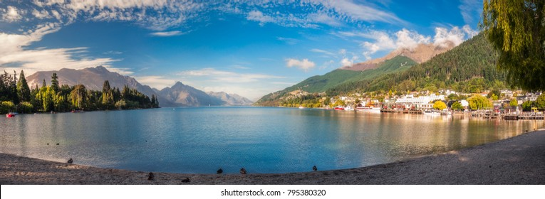 Early morning at the beach on lake Wakatipu in Queenstown, with the wharf on the right hand side and Queenstown Gardens of the left and Southern Alps in the background.