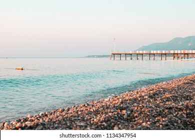 Early morning beach pier and sea against clear skyline in Kemer, Turkey
