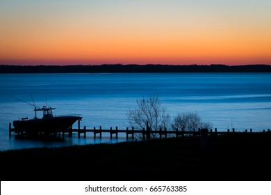 Early morning before sunrise silhouette of a boat and a dock on the Rappahannock River in Virginia