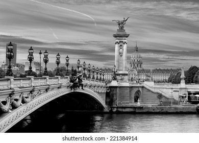 Early morning, black and white, view on the famous landmark Alexander iii bridge in Paris, capital of France, with beautiful clouds in the sky and the golden statue catching the first sunrays
