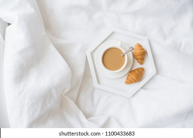 Early morning breakfast in bed, coffee and croissant on the tray