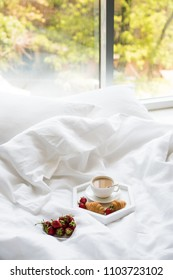 Early morning breakfast in bed, coffee and croissant with strawb