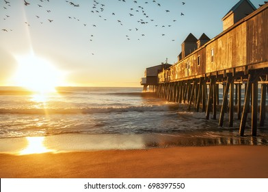 Early morning by the ocean. Wooden old pier leaving in the sea with wooden buildings. Birds flying in the sky. USA. Portland. Maine.
