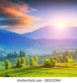 Early morning in a Carpathian mountain valley with green meadow and colorful clouds in beautiful light of sunrise