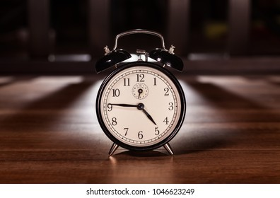 Early morning clock in dark setting with artificial back light