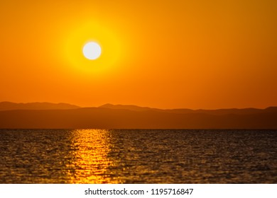 Early morning , dramatic sunrise over sea and mountain. Photographed in Asprovalta, Greece.