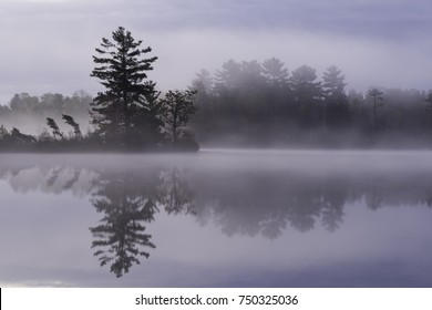 Early morning fog drifts silently across the surface of a secluded North Woods lake in northern Wisconsin.