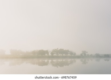 Early morning fog over lake with tree reflections