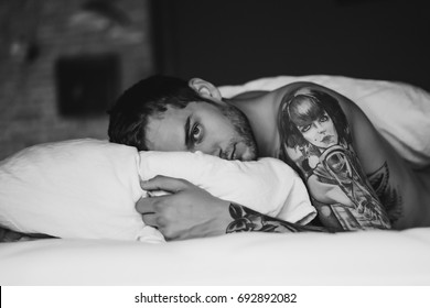 Early morning, gentle morning, a tattooed man in bed wakes up and starts a new day. A man on a pillow with a bristle smiling