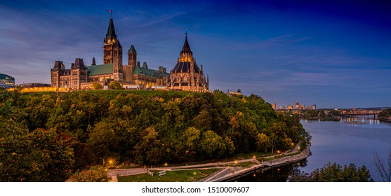 Early morning golden hour sunlight illuminates the gothic revival architecture of the Canadian Parliament and Parliament Library buildings over looking the Ottawa river at sunrise in early autumn.