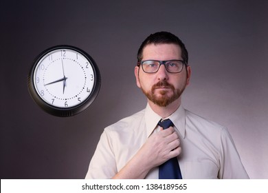 Early morning grumpy looking bearded man with glasses in shirt dressing up adjusting necktie with a clock in the background. Studio shot of business, men style, clothes concept. Daily lifestyle.